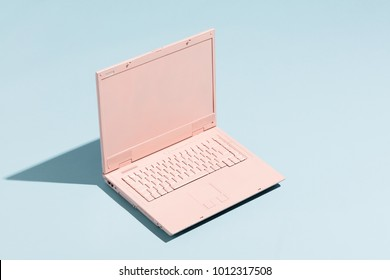 Retro pink laptop on a pastel blue background. Technology. Creativity and minimalism.