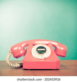 Retro pink telephone on wood table front mint green gradient background
