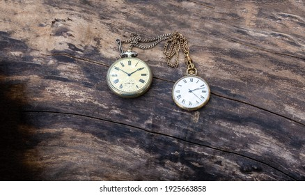 Retro pocket watch lie on a wooden background. Vintage style and filtered process.