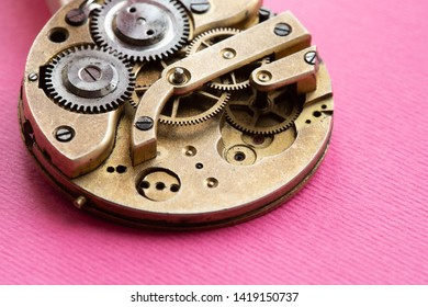 Retro pocket watch mechanic clockwork mechanism, spring bronze cogs wheels macro view. Shallow depth of field, selective focus. Pink background