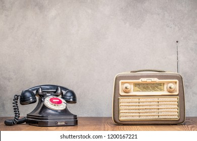 Retro portable broadcast radio receiver and black rotary telephone from circa 1950s on wooden table front textured concrete wall background. Listen music concept. Vintage old style filtered photo