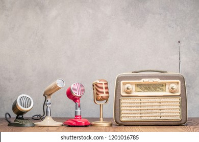 Retro portable broadcast radio receiver from circa 1950s and four microphones front textured concrete wall background. Interview or press conference concept. Vintage old style filtered photo