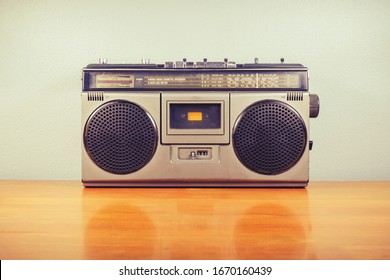 Retro portable radio with cassette player on wood table, outdated stereo boombox in vintage color - Shutterstock ID 1670160439