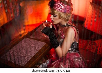 Retro portrait of a beautiful Gatsby woman with a martini glass. Vogue fashion style and smoke