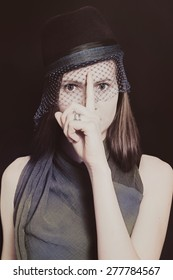 Retro portrait of a beautiful young woman in a hat with a veil on a black background