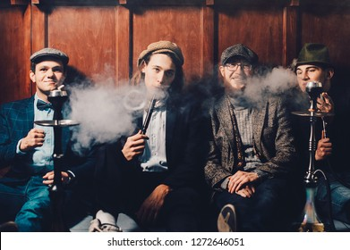 Retro portrait of four young people smoking hookah in a bar while talking. Concept of having a good time in retro style. sitting on the floor near the bar view