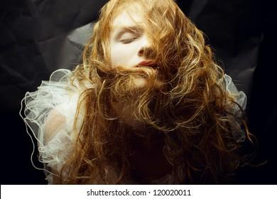 Retro portrait of red-haired (ginger) queen like girl over wrinkled black paper background. studio shot