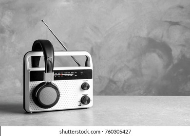 Retro radio and headphones on table against grey wall