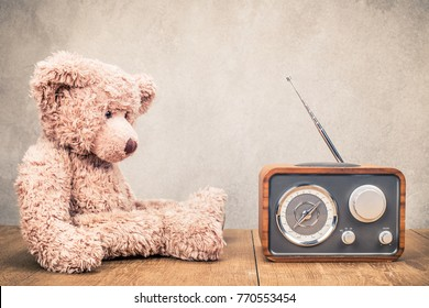 Retro radio receiver and old plush Teddy Bear toy on wooden table front concrete wall background. Listen music concept. Vintage instagram style filtered photo