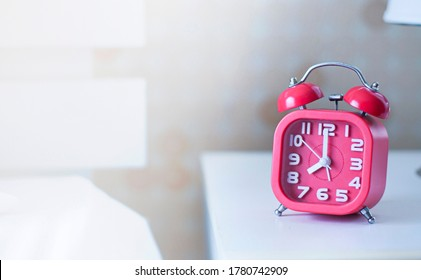 Retro red alarm clock on table in bedroom for waking up at morning .