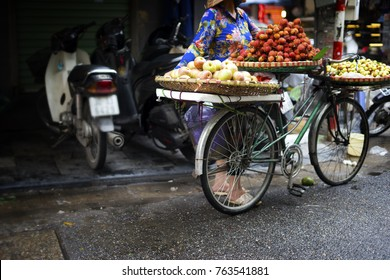 Retro red bike in fruit market. Daily life of the fruit sell on her bicycle in the typical street in old town at Hanoi city, Vietnam. This is small market for retailers and hawkers.