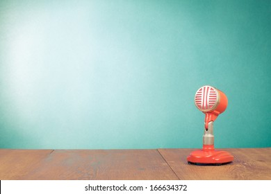 Retro red microphone on table front mint green background
