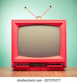 Retro red old television from 80s front mint green wall background