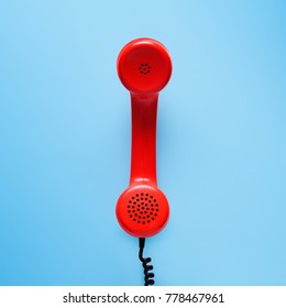 Retro red telephone on blue background.