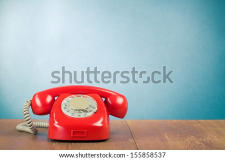 Retro red telephone on wood table near aquamarine wall background