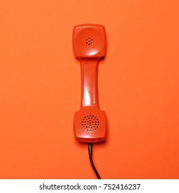 Retro red telephone tube on orange background - Flat lay