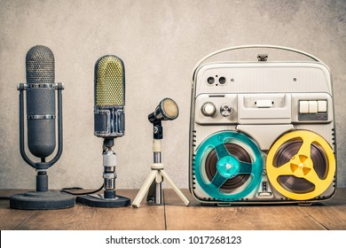 Retro reel to reel tape recorder circa 70s and studio microphones on wooden table front concrete wall background. Vintage style filtered photo