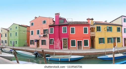 Retro residential houses with colorful facades on Burano island with small boats in canal