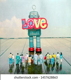retro robot holding a bright colorful cloch love sign to a crowed of plastic people  on a old wooden floor