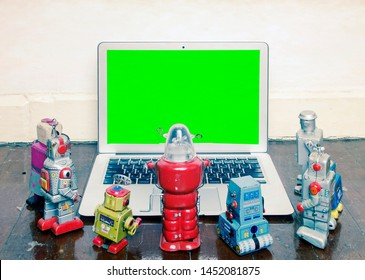retro robot toys gather around a laptop on an old wooden floor