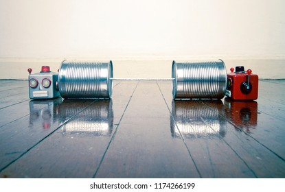 retro robots on tin can phones on a wooden floor with reflection