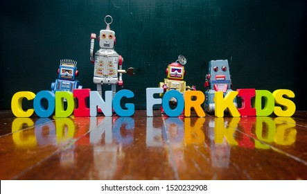 retro robots and the words CODING FOR KIDS on a old wooden floor
