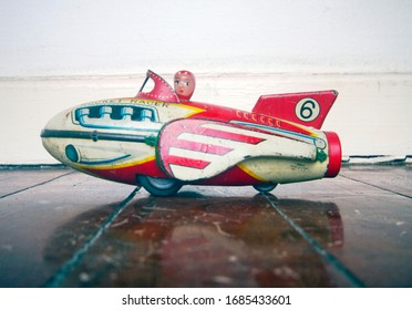 retro rocket toy with girl pilot on a old wooden floor