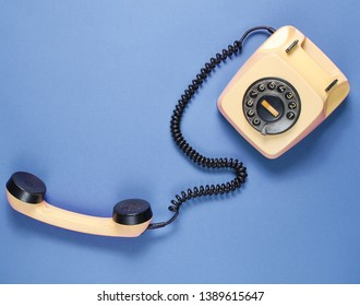 Retro rotary phone with handset on blue background. Top view