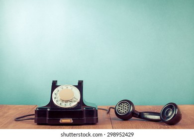 Retro rotary telephone on table in front mint green background. Old instagram style filtered photo