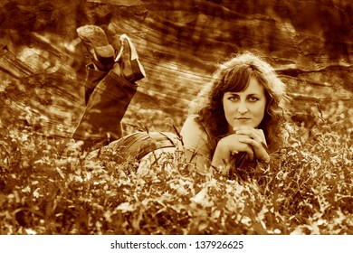 retro sepia photo curly-haired girl is woman in jeans and t-shirt lying on green grass
