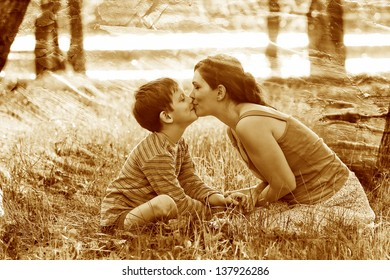 retro sepia photo, Mom and son of woman and child sitting on grass kissing at sunset Romantic