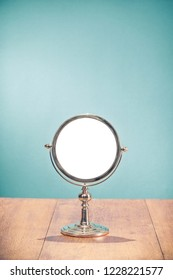 Retro silver makeup mirror frame on aged oak wooden table front mint blue wall background. Vintage style filtered photo