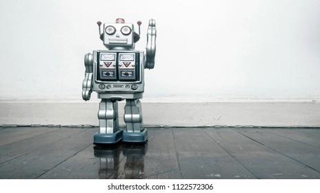 retro silver robot waving hi on an old wooden floor