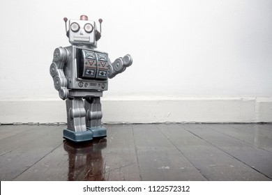 retro silver robot waving hi on an old wooden floor