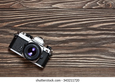 Retro SLR camera on old wooden background