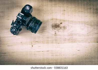 Retro SLR camera on wooden desk in vintage style with copy space