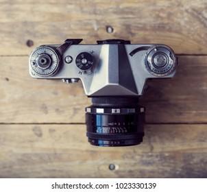 Retro slr photo camera over wooden background. Vintage camera.
