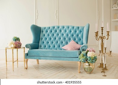 Retro sofa in mint color in the interior. flowers in vases and candles in sconces