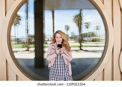 Retro solo traveller girl using smart phone, leaning against wood glass circles graphic reflections, sunny outdoors. Tourist female on holiday using technology, travel recreation leisure lifestyle.