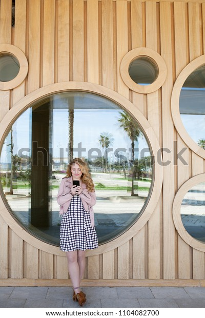 Retro solo traveller girl using smart phone, leaning circles graphic reflections, sunny destination outdoors. Tourist female smiling on holiday using technology, travel recreation leisure lifestyle.