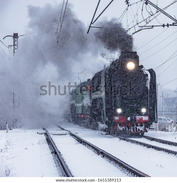 Retro steam train moves at winter snowy time.