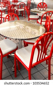 Retro steel or metallic tables and red chairs at a diner or restaurant