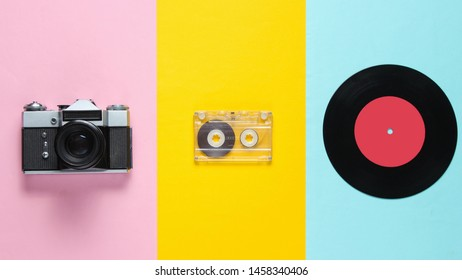 Retro still life, 70s. Vinyl record, audio cassette and film camera on pastel background. Top view. Flat lay