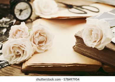 Retro still life with vintage rose flowers and open ancient book. Nostalgic composition on old wooden table