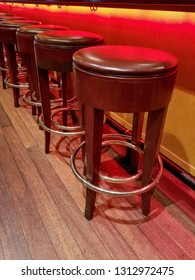 retro stools in a row on wood floor under bar counter with red neon lighting