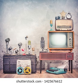 Retro studio microphones set, outdated TV, old broadcast radio, journalist's reel to reel tape recorder, aged clock, film camera, golden award star, typewriter. Journalism concept. Vintage style photo