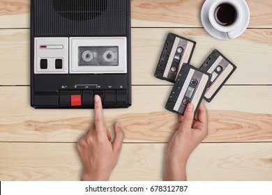 Retro stuff, old items, memories. Hands switching on old tape cassette recorder and holding three cassettes choosing which song to reproduce. Woman listening to old songs remebering her youth