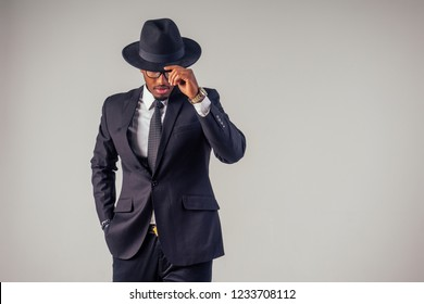 Retro style African american business man mafia model in dark suit and black hat in studio on white background