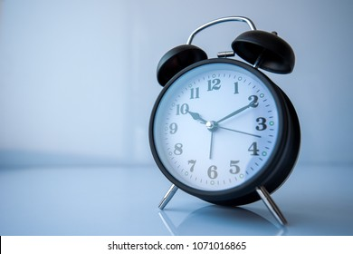 Retro style analog black alarm clock shows 10 hours and ten minutes