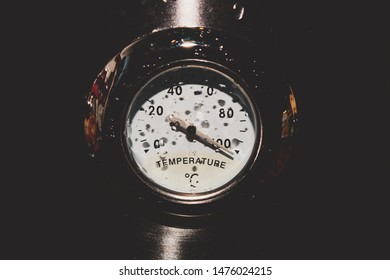Retro style analog thermometer on the metal background. high temperature concept